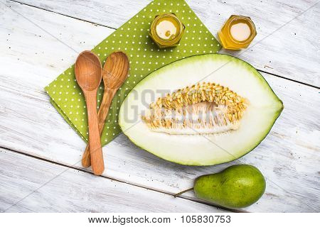 Ripe Melon Spoons Honey And Pear On White Wood