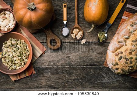 Rustic Pumpkins With Bread And Seeds On Wood