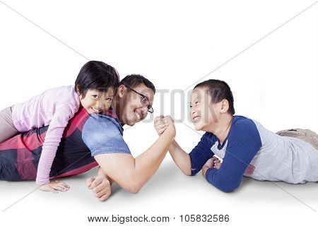 Portrait of young father playing with his children and arm wrestling with his son isolated on white