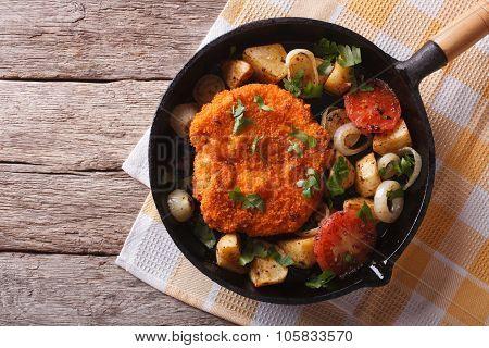German Weiner Schnitzel With Vegetables In A Pan. Horizontal Top View