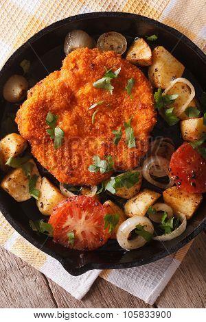 Weiner Schnitzel, Fried Potatoes In A Pan Closeup. Vertical Top View
