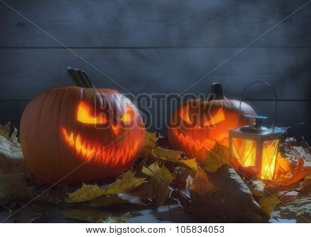 Spooky Pumpkins Jack O Lantern Among Dried Leaves On Wooden Fence