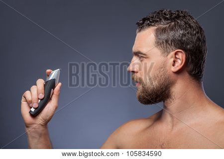 Attractive bearded guy is expressing hesitation about shaver