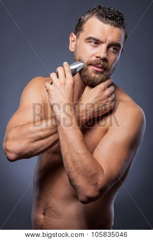 Handsome bearded guy is caring of his appearance