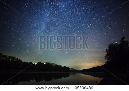 a beautiful night sky the Milky Way star trails and the trees