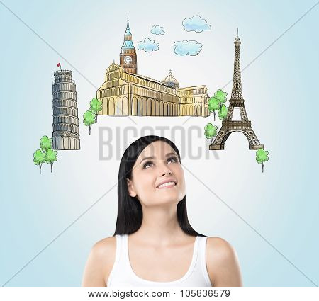 A Beautiful Brunette Is Looking Up By Dreaming About The Visiting Of The Most Famous European Cities