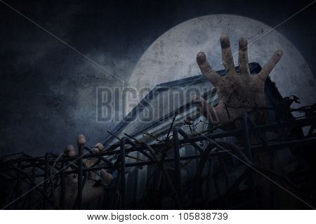Hand Over Metal Fence With Dry Leaves Over Old Building And Moon, Halloween Concept