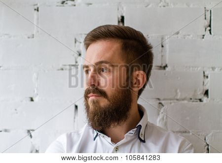 Young bearded man looking at the window