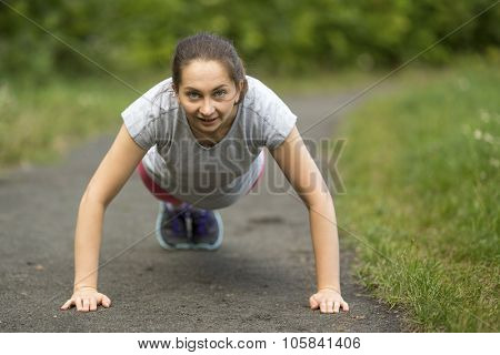 Young girl doing push-ups from the ground, a warm up before your jog outdoors.