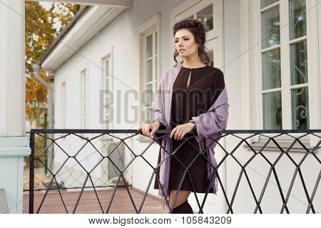 beautiful pretty woman in a brown dress in a shawl over his shoulders came out on the veranda