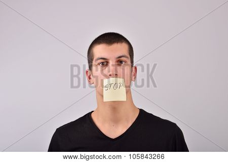 Teenager With Stop Note On His Mouth