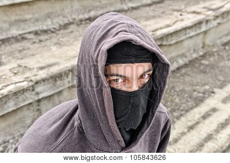 Unrecognizable Young Man Wearing Black Balaclava Sitting On Old Stairs, Looking At The Camera