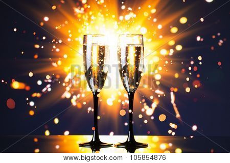 champagne glasses against sparkler background