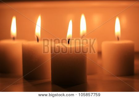 Holiday candles burning on a white background and reflected.