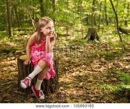 Happy Young Girl Sitting In Woods Looking At Copy Space
