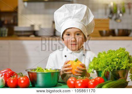 Little smiling Chef boy preparing healthy food at kitchen. the concept of vegetarianism
