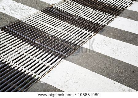 Rusty Metal Ventilation Grille Painted In Zebra Crosswalk On Asphalt Way.