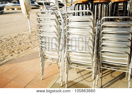 Metal Chairs Stacked In The Restaurant On The Sandy Beach On A Sunny Day.