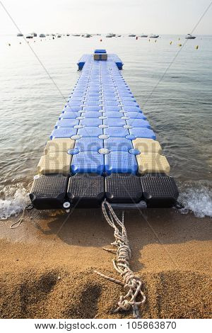 Plastic Blue Jetty In The Empty Sea Against Blue Sky.