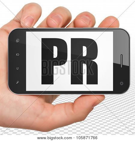 Marketing concept: Hand Holding Smartphone with PR on display