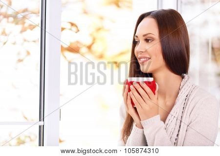 Attractive young lady holding a cup.