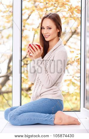 Attractive young lady with a cup on the windowsill.