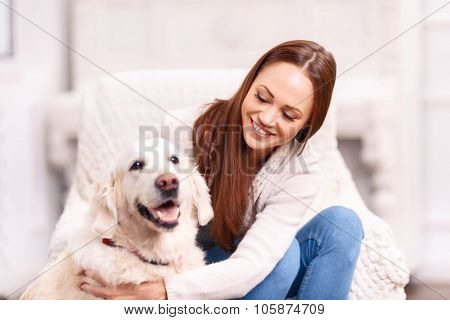 Young girl patting her pet dog.