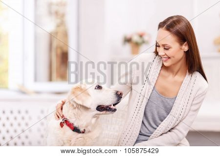 Attractive young girl is playing with her dog.