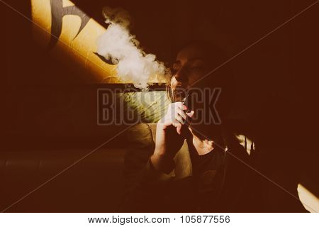 girl sits and smokes electronic cigarette