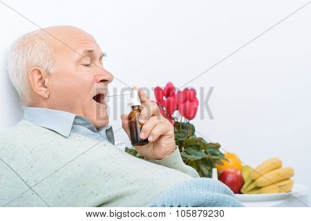 Weary senior gentleman uses his sore throat spray.