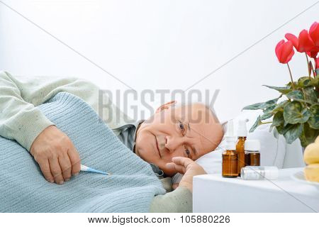 Senior aged man is resting while holding a thermometer.