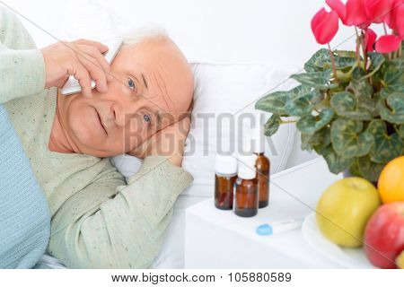 Worried elderly patient is calling somebody.
