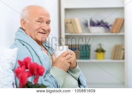 Elderly gentleman grins happily while resting.
