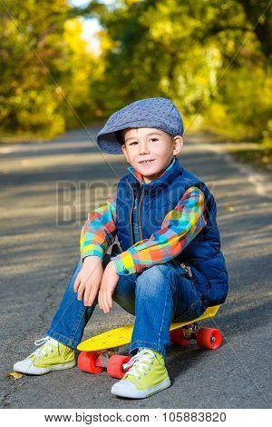 Smiling boy sitting on color plastic penny board skateboard at park
