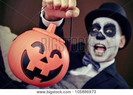 a man with mexican calaveras makeup, wearing jacket, bow tie and top hat, holds a carved pumpkin