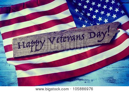 the text happy veterans day written in a piece of wood and a flag of the United States, on a blue rustic wooden background
