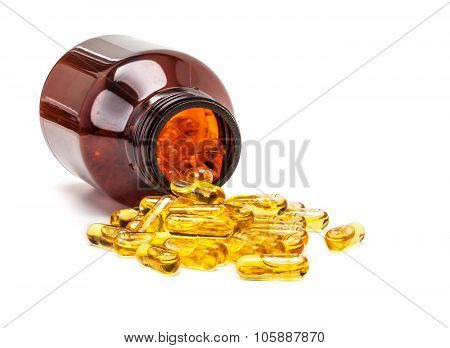 fish oil capsules spilling out from brown glass bottle