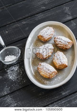 Cookies Madeleines With Powdered Sugar On Oval Plate On A Light Wooden Surface