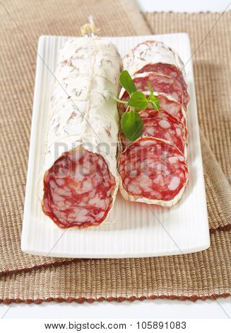 sliced french dry salami on white rectangular plate and brown place mat