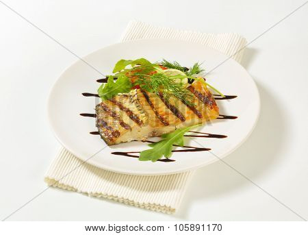 grilled carp fillet with lemon, dill, arugula and tomato on white plate and place mat