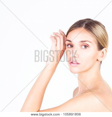 Young woman with smooth skin holding her hand to her forehead