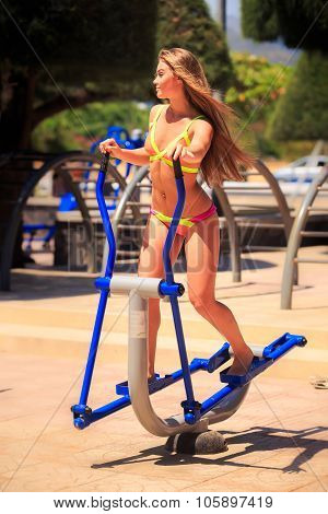 Blonde Girl In Bikini Trains On Stepper In Park Near Beach