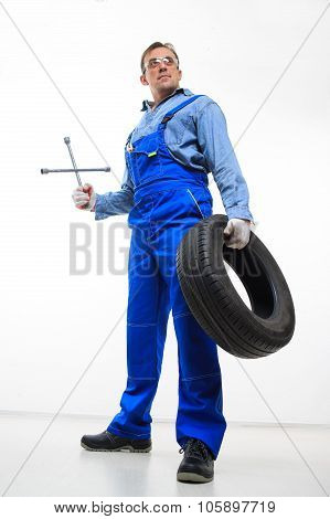 adult male mechanic with a wrench and tire
