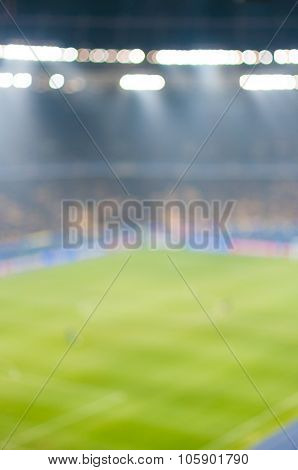 Blurred Green soccer field, bright spotlights, illuminated stadium