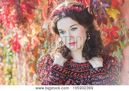 Portrait of fairy autumn girl with red fall wreath at floral background of grape woodbine