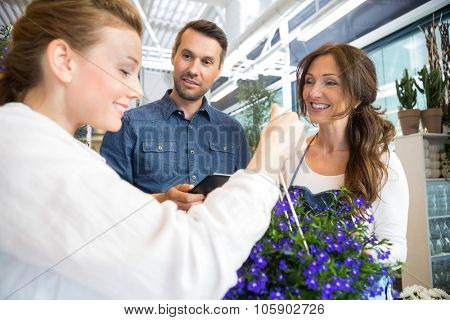 Mid adult florist assisting couple in buying purple flower plant at store