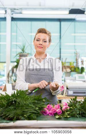 Portrait of confident female florist cutting stem on rose in flower shop