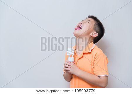 Asian Boy Joking Gesture Licking Fake Ice Cream Made With Energy Saving Lamp, Concept Idea
