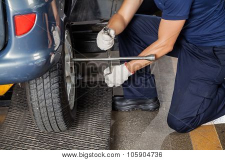 Low section of mechanic using rim wrench to fix car tire at garage