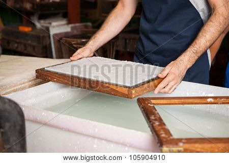 Midsection of male worker dipping mold in pulp and water at paper factory